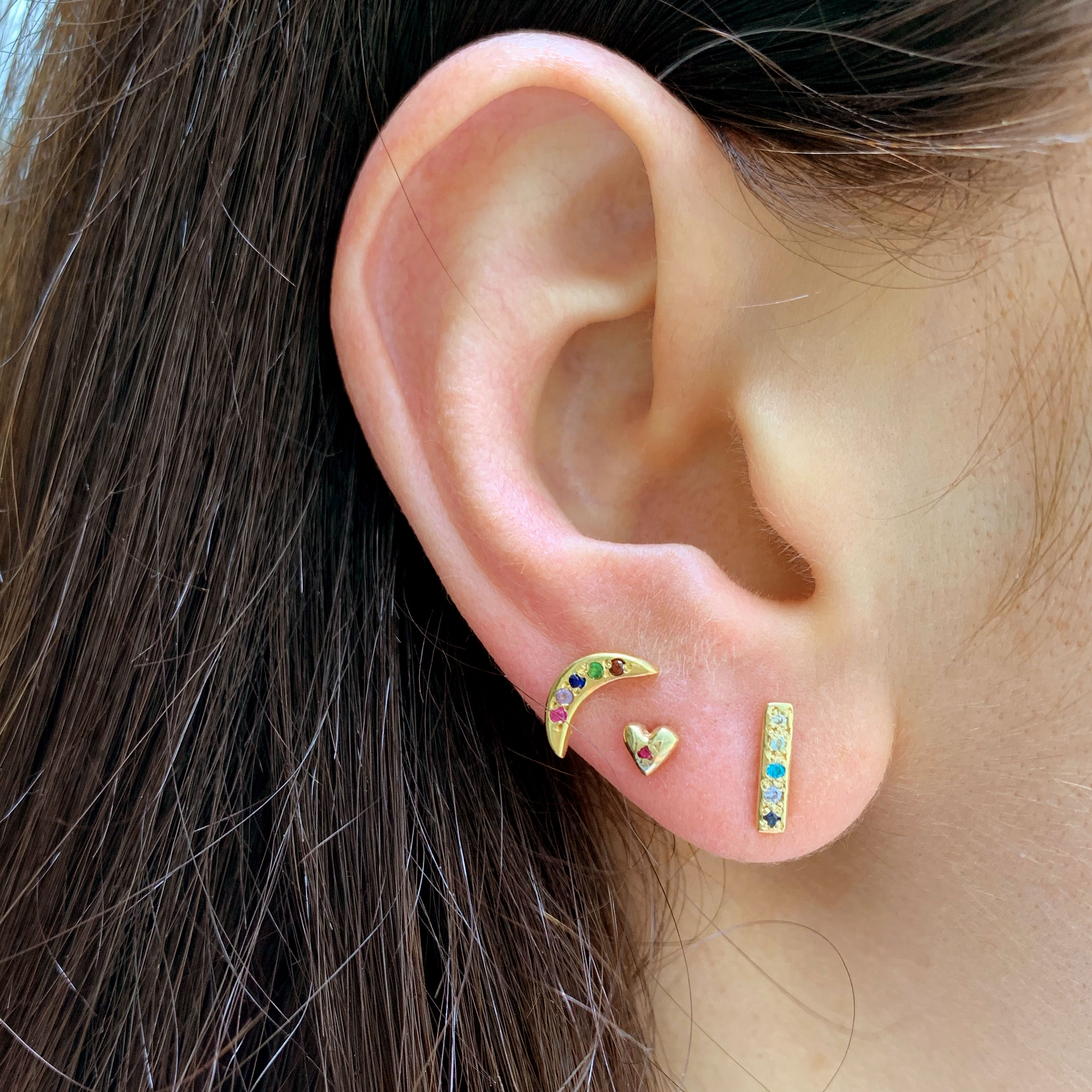 Wearing tiny mini stud earrings in yellow gold